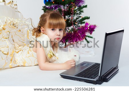 The little girl is dressed in a festive dress with a white rabbit and a laptop. Decorated Christmas tree in the background.