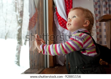 The little girl is looking out the window at the cafe
