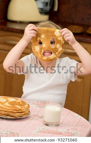 The little girl is naughty behind a table on kitchen - stock photo