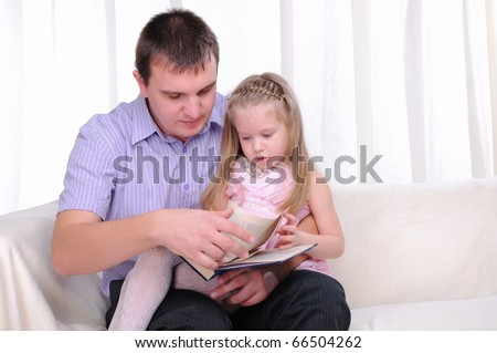 The little girl is sitting on the lap of his father, and reads with him a book.