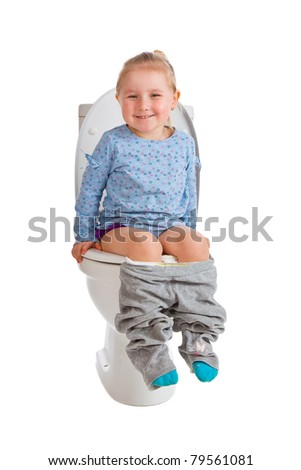 the little girl is sitting on toilet - stock photo
