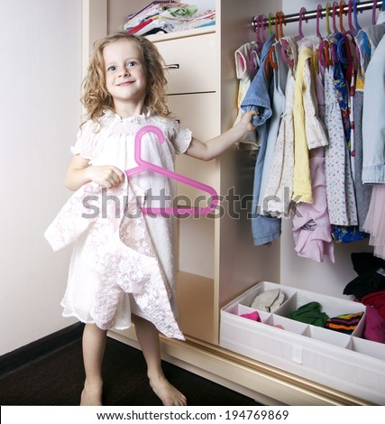 the little girl is smiling and chooses clothes