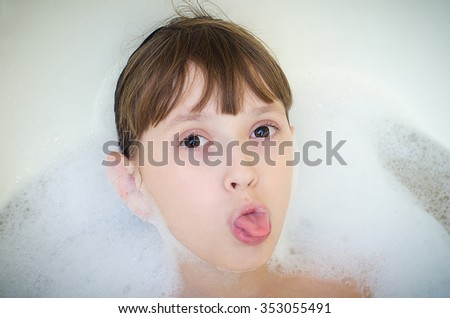 The little girl lies in a bathroom with foam and puts out the tongue