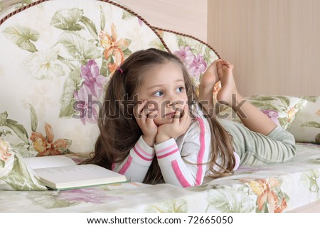 The little girl lies on a sofa and reads the book - stock photo