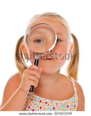 the little girl looking through a magnifying glass. Studio shot. - stock photo