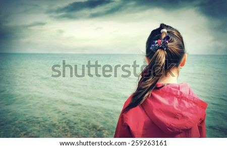 The little girl looks at the sea - stock photo