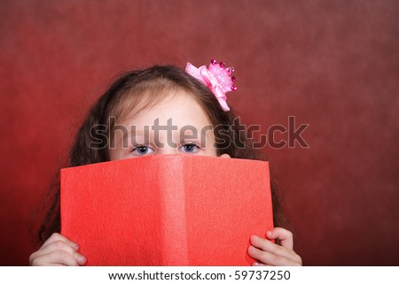 the little girl looks out behind the book - stock photo