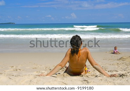 The little girl on a beach with mum