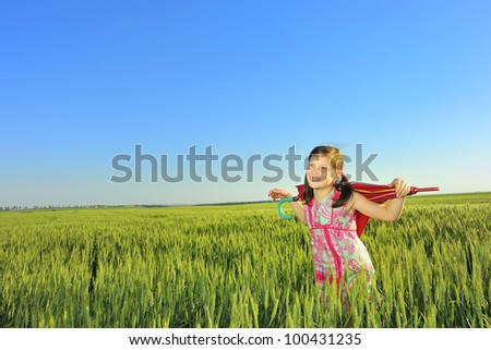 The little girl on a field with an umbrella - stock photo