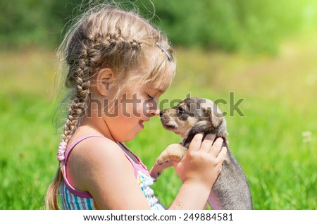 The little girl on a lawn with a puppy in the sunny day - stock photo