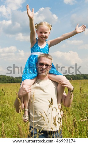 the little girl on her fathers shoulders - stock photo