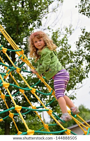 The little girl on jungle gym - stock photo