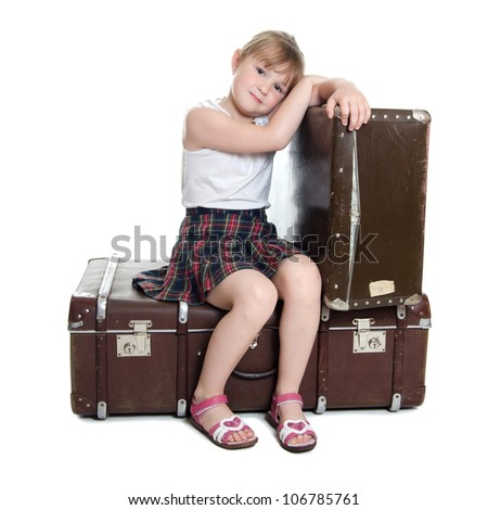 The little girl on old suitcases isolated - stock photo