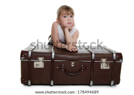 The little girl on old suitcases isolated