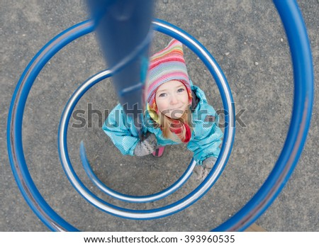 the little girl on the Playground in blue overalls and a funny hat - stock photo