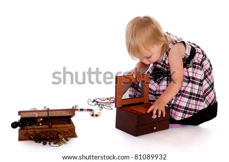 The little girl opens a box with a beads - stock photo