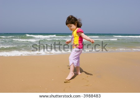 The little girl plays on seacoast - stock photo