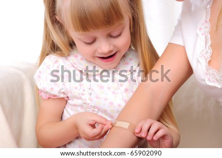 the little girl puts a plaster on his mother's hand - stock photo