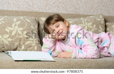 The little girl reads the book lying on a sofa. A house room