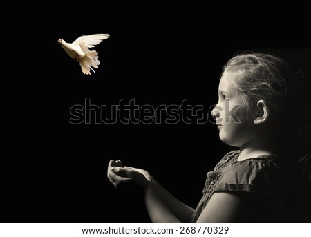 The little girl releasing a white dove from hands . Symbol of peace on a black background. MANY OTHER PHOTOS FROM THIS SERIES IN MY PORTFOLIO.