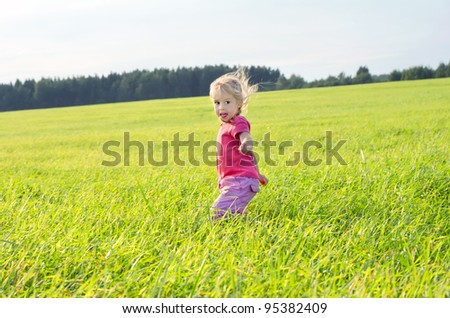 The little girl runs across the field on a decline - stock photo