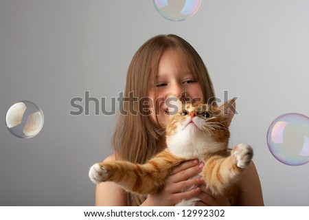 The little girl sits, holds a red cat, and it catches soap bubbles - stock photo