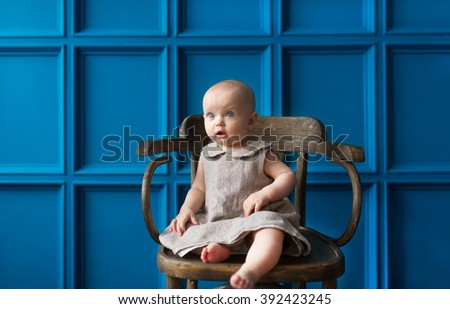 The little girl sits on a chair against a blue wall. - stock photo