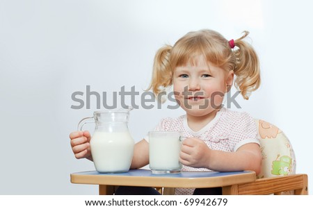 The little girl sits on a chair and has control over a cup with milk