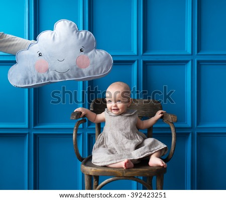 The little girl sits on a chair. The father holds over the head the girl a pillow in the form of a cloud. - stock photo