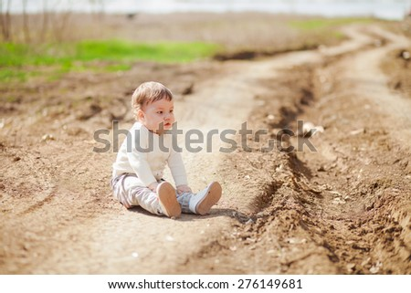 the little girl sits on an earth footpath, selective focus