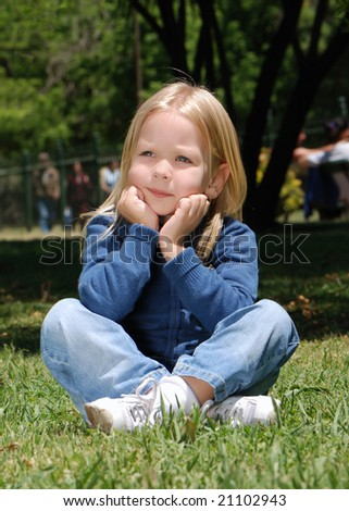 The little girl sitting on a grass in park
