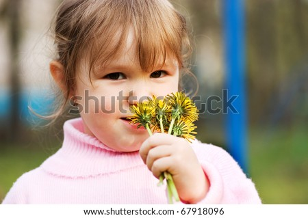 The little girl smells flowers - stock photo
