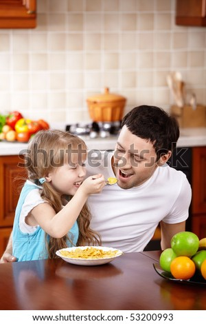 The little girl spoon-feeds the daddy on kitchen - stock photo