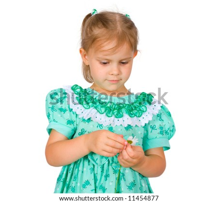The little girl tears off petals at a camomile - stock photo