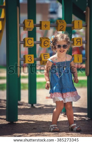 The little girl walks outdoors in the summer on the playground Girl playing and studying letters