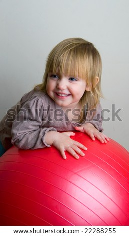 The little girl with a greater red ball