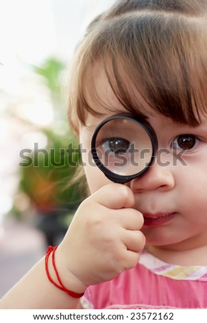 The little girl with a magnifier - stock photo
