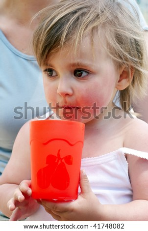 The little girl with a water glass - stock photo