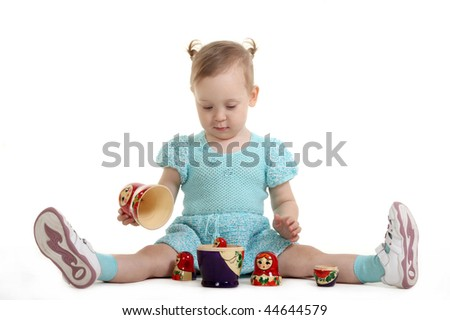 The little girl with enthusiasm plays with Russian nested doll - stock photo