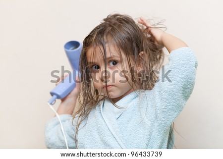 The little girl with hairdryer in the hands drying her hair - stock photo