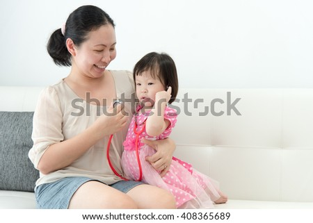 The little girl with her mother played in doctors - stock photo