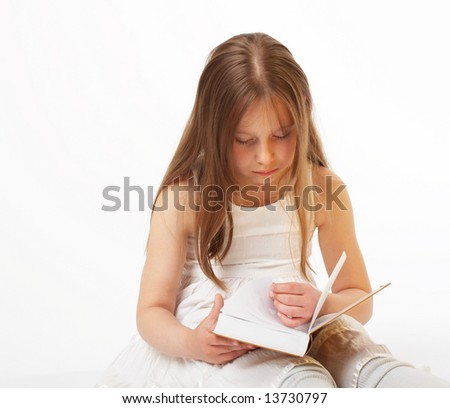 The little girl with long hair sits and reads the book