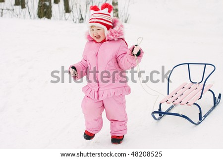 The little girl with sledge in the winter - stock photo