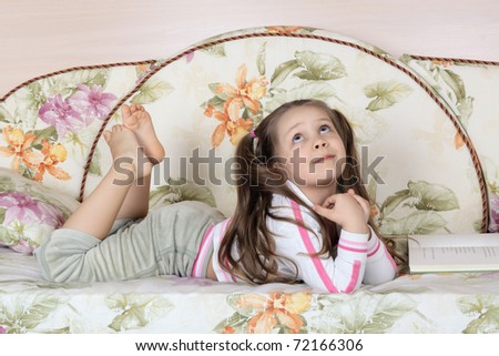 The little girl with the book lies on a sofa and pensively looks upwards - stock photo