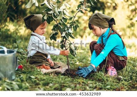 The little girls gardener playing in garden. - stock photo