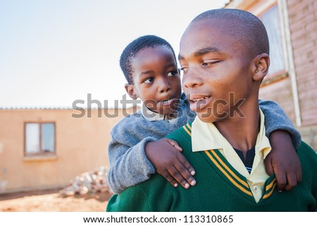 The little guy is mocking his big brother. - stock photo