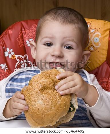 The little happy boy eating a tasty hamburger - stock photo
