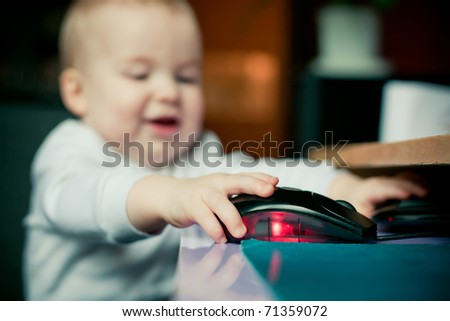 the little happy boy using computer mouse - stock photo