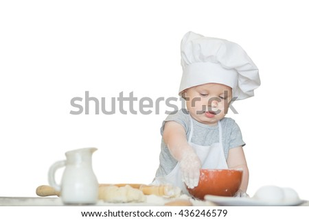 The little kid boy in a suit of the cook sculpts dough. Baby scullion make dinner in chef suit isolated on white. Cooking concept with free text space - copy space