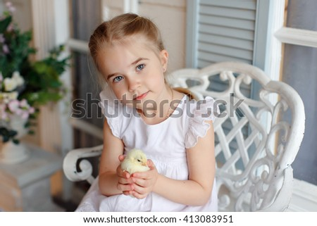 The little red-haired girl with pigtails holding a yellow chicken on a background of white houses and flowers - stock photo